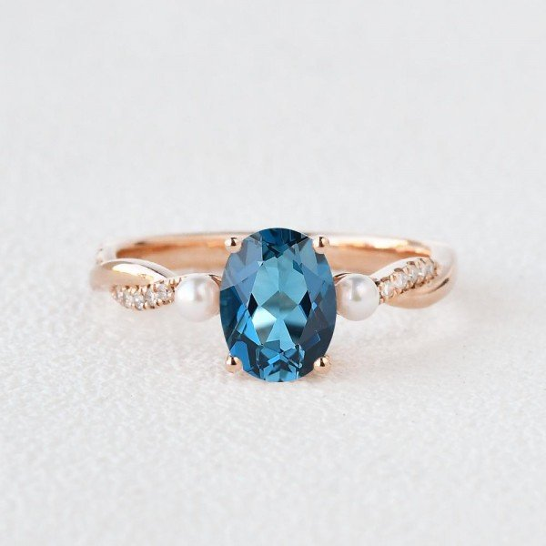 Oval Shaped Blue Topaz Trinity Twist Ring - Rose - Front