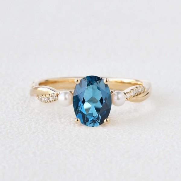 Oval Shaped Blue Topaz Trinity Twist Ring - Yellow - Front